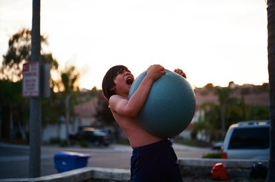 Boy's Hugging Yoga Ball While Opening Mouth