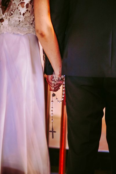 Bride and groom holding hands with the rosary