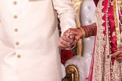 Bride in Red And Gold Dress Holds Hands with Groom in