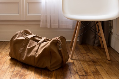Brown Duffel Bag Beside White And Brown Wooden Chair