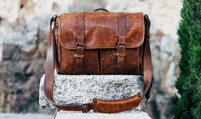 Brown Leather Satchel Bag on Gray Concrete Surface Near Green Plant