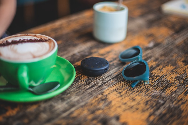 Ceramic Mug on Saucer Beside Sunglasses