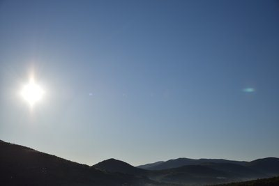 Clear Sky And Glaring Sun Over Hillside