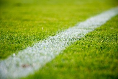 Close-Up of A White Line on Green Grass in A Soccer