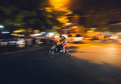 Couple Riding on Black Motor Scooter at Nighttime