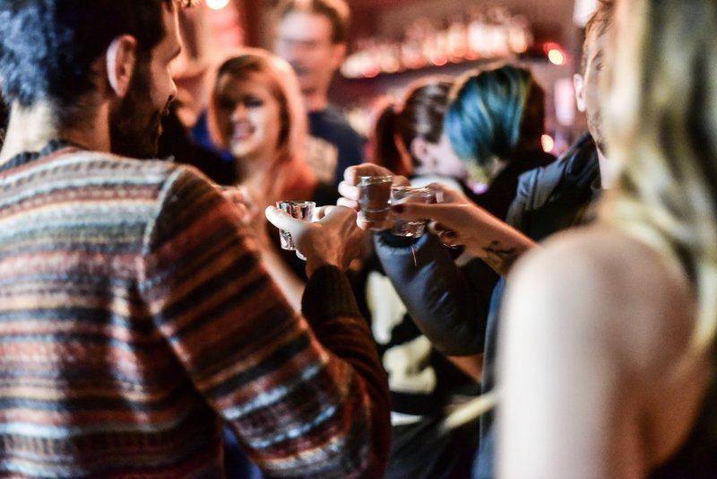 Friends Cheers With Shot Glasses In Bar