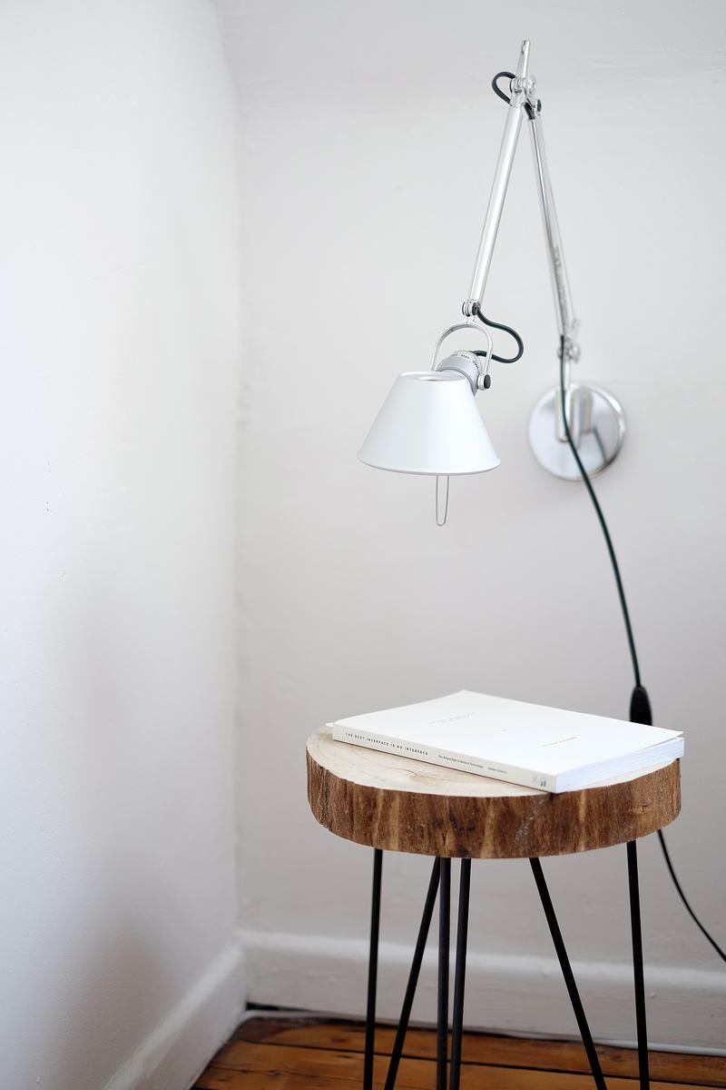 Gray Desk Lamp Mount on White Wall Under Brown Stool with