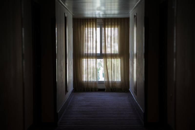Hallway Leading To Window Covered By Brown Window Curtain