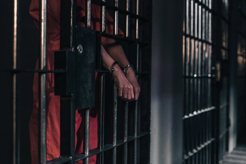 Hands In Handcuffs In A Prison Cell