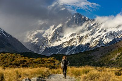 Hiker Approaches Snow-capped Mountains
