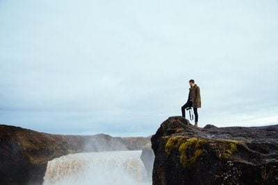 Hiker On Cliff By Waterfall