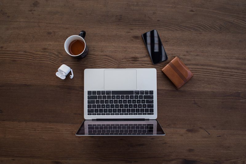 Laptop With Wallet, Phone, Earbuds, And Tea