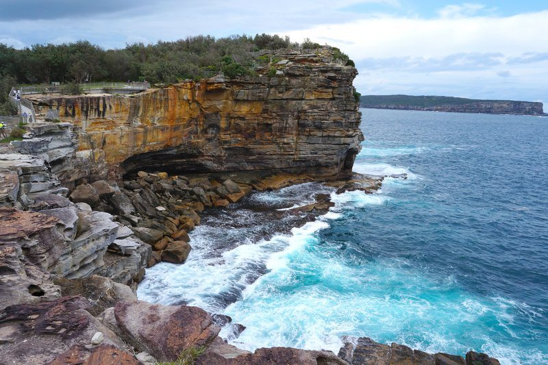Layers Of Rocky Cliffs By Crashing Ocean Waves