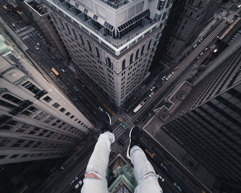 Legs Dangling Over A Heart-Stopping Drop To The City Below