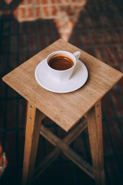 Long Espresso Sits On A Wooden Stool