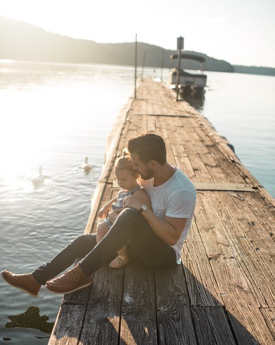 Man And Girl Sitting on Brown Dock Near Boat And Two