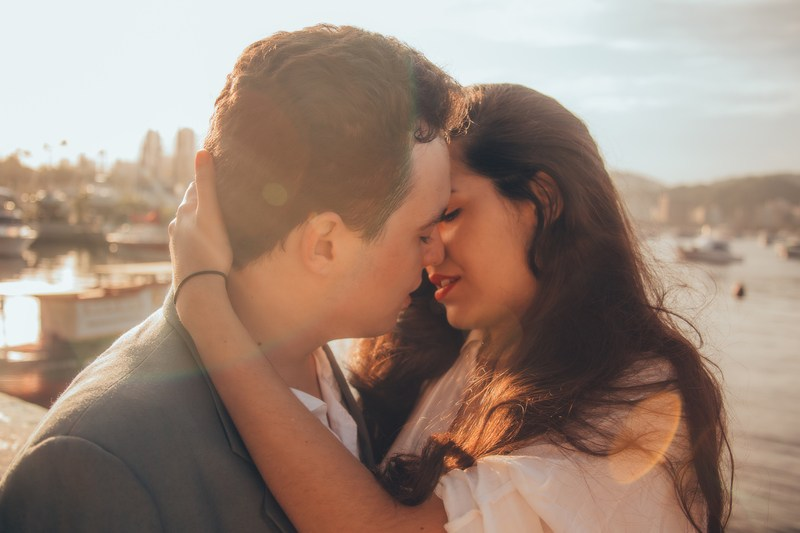 Man And Woman Kissing Beside Bay