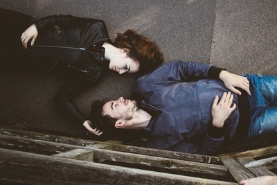 Man And Woman Lying on Gray Concrete Surface Looking At Each