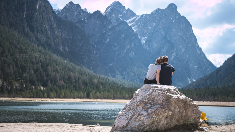 Man And Woman Sitting on Rock Near Water And