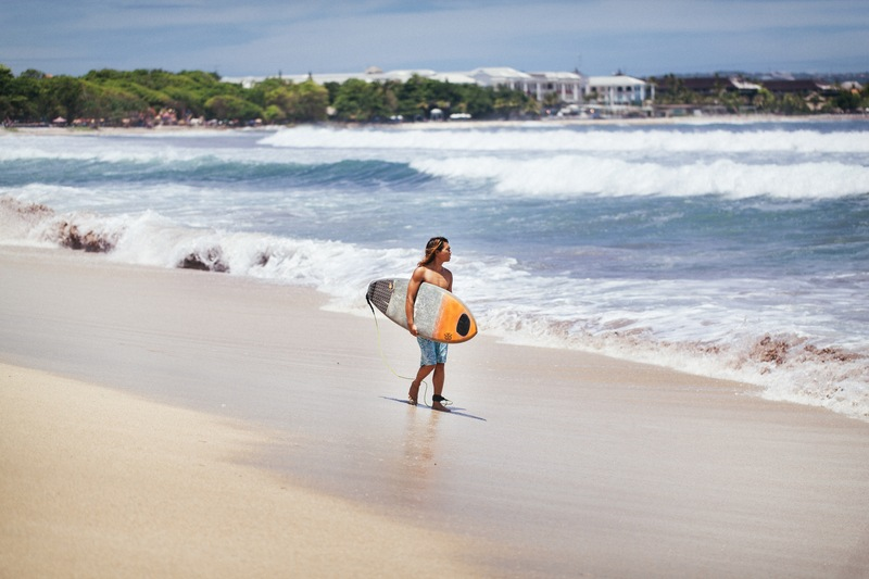 Man Carrying Yellow And White Surfboard Standing Near Beach