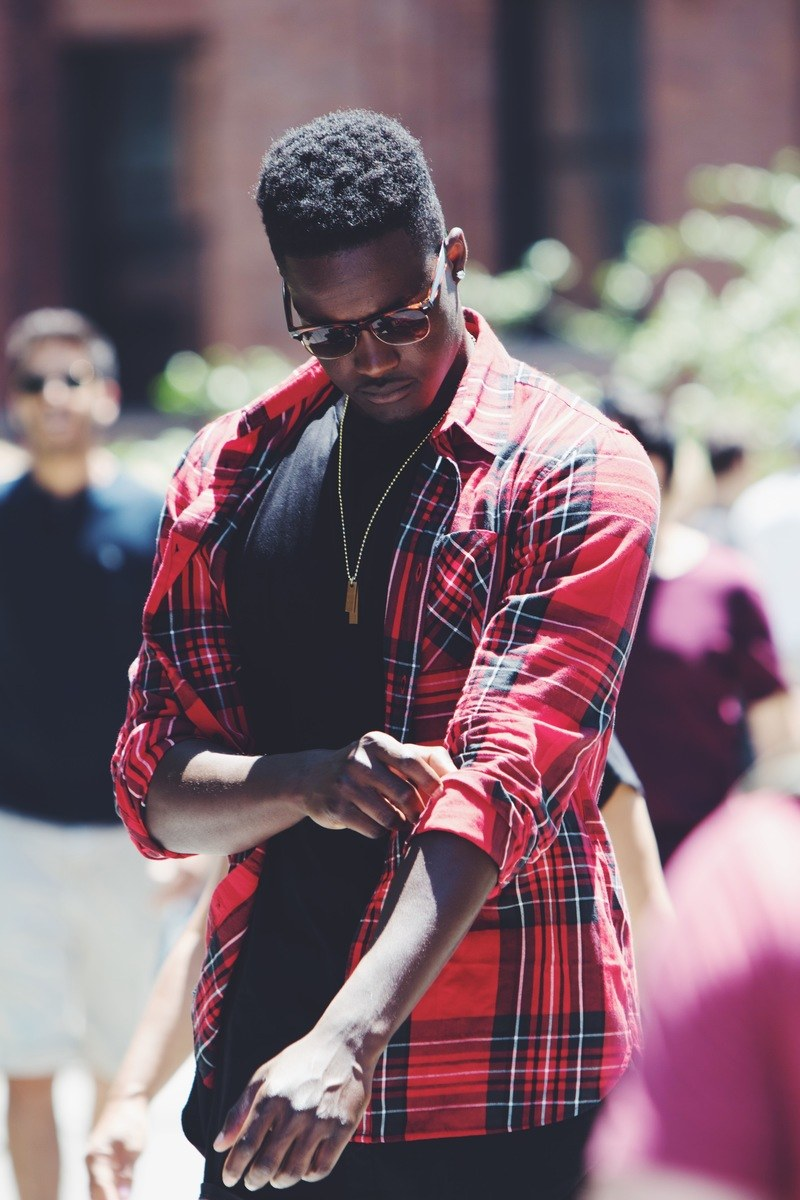 Man Fixing His Red, Black, And White Plaid Sport Shirt Sleeve