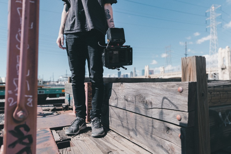 Man Holding Black Video Camera While Standing on Plank