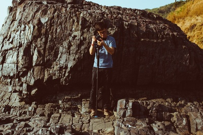 Man Holding Camera While Standing on Cliff