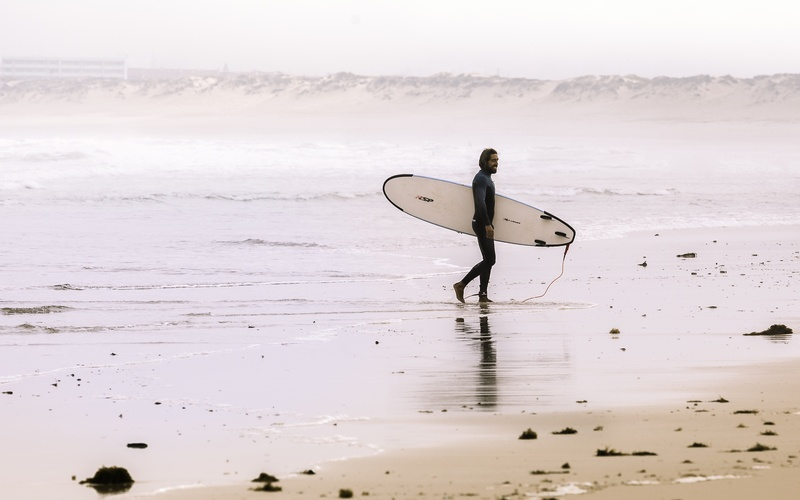 Man Holding Surf Board While Standing on Shore