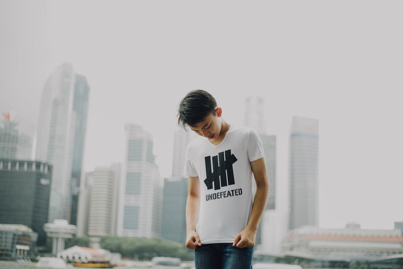 Man Looking At His Shirt with Buildings Background