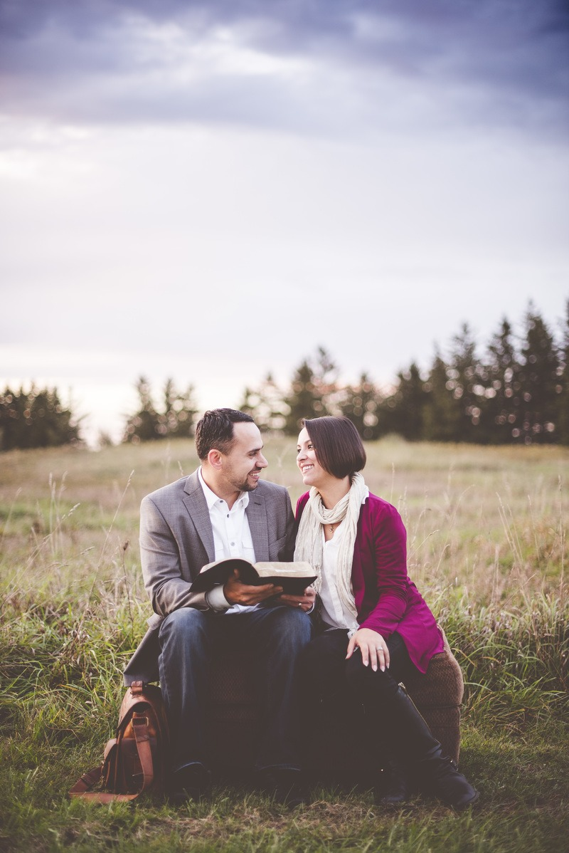 Man Reading Book To Woman Under Grey Cloudy Sky