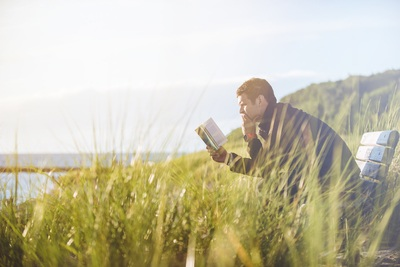 Man Reading Book on Beach Near Lake
