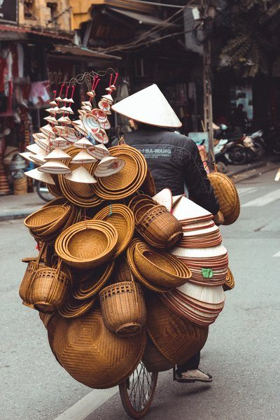 Man Riding Bicycle With Bowls And Baskets