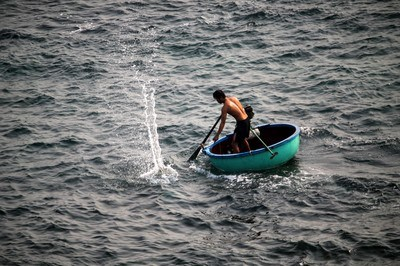 Man Riding on Round Green Boat