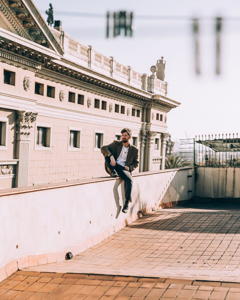 Man Sit Casually On Roof Ledge