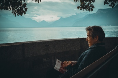 Man Sitting While Holding A Book Watching in Water
