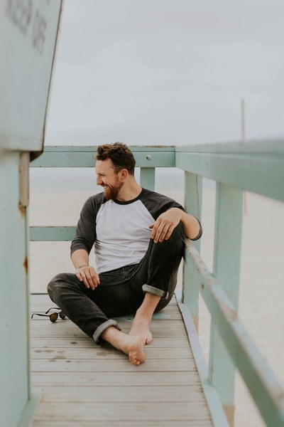 Man Smiling While Sitting on Floor