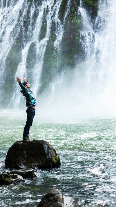 Man Standing on Black Rock Surrounded Water