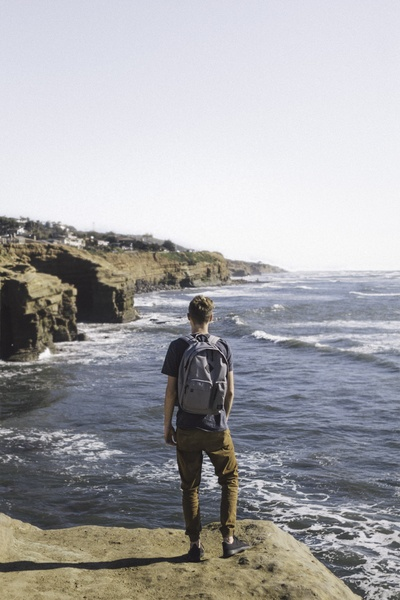 Man Standing on Cliff Looking Water