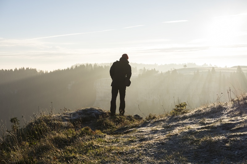 Man Standing on Cliff Near Trees