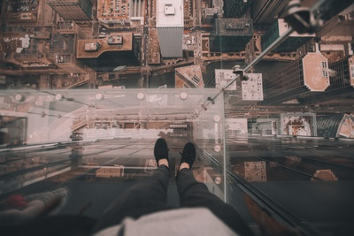 Man Standing on Glass Platform on Top of Building Looking Down