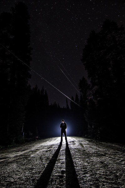 Man Standing on Pathway at Nighttime