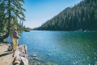 Man Standing on Rock on Front of Lake Surrounded with Trees
