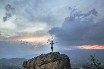 Man Standing on Top of Rock Mountain