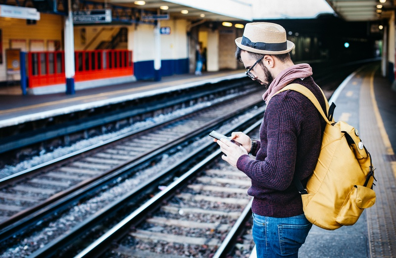 Man Using Phone While Standing in Front of Train Rail During