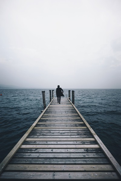 Man Walking on Dock Surrounded By Ocean