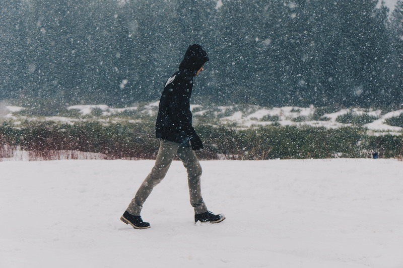 Man Walking on Snow-Covered Road