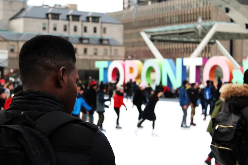 Man Wearing Black Backpack Ice Skating with Other People Near Toronto