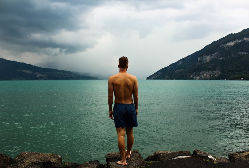 Man Wearing Black Shorts Standing in Front of Water