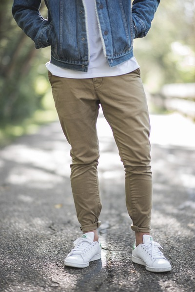 Man Wearing Brown Fitted Jeans And Sneakers Standing on Road At