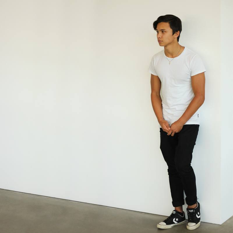 Man Wearing White T-Shirt And Black Jeans Standing Near White Wall